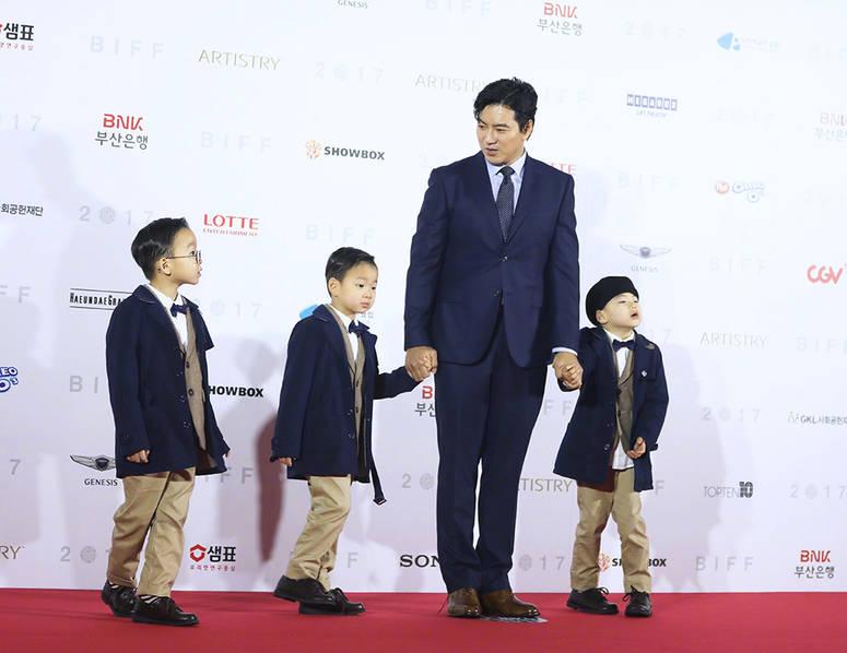 第22届釜山国际电影节在雨中开幕,关注度最高的就是曾经在韩国真人秀节目中大火的《宋家三胞胎》,在很多人的印象中大韩民国万岁还停留在小时候的模样,但是在釜山电影节上没想到兄弟三个都长这么大了,样貌没有发声什么改变,个子长了很高了。  宋一国携三胞胎儿子一齐亮相,三小只西装革履,红毯上更是一点也不拘束,各自小表情,非常可爱。  大韩、民国、万岁2014年随着爸爸宋一国出演亲子节目《超人回来了》,3位萌娃圆滚滚又活泼淘气的模样掳获不少观众的心。虽然不久后便离开节目,但爸爸仍会在Instagram上分享孩子们的